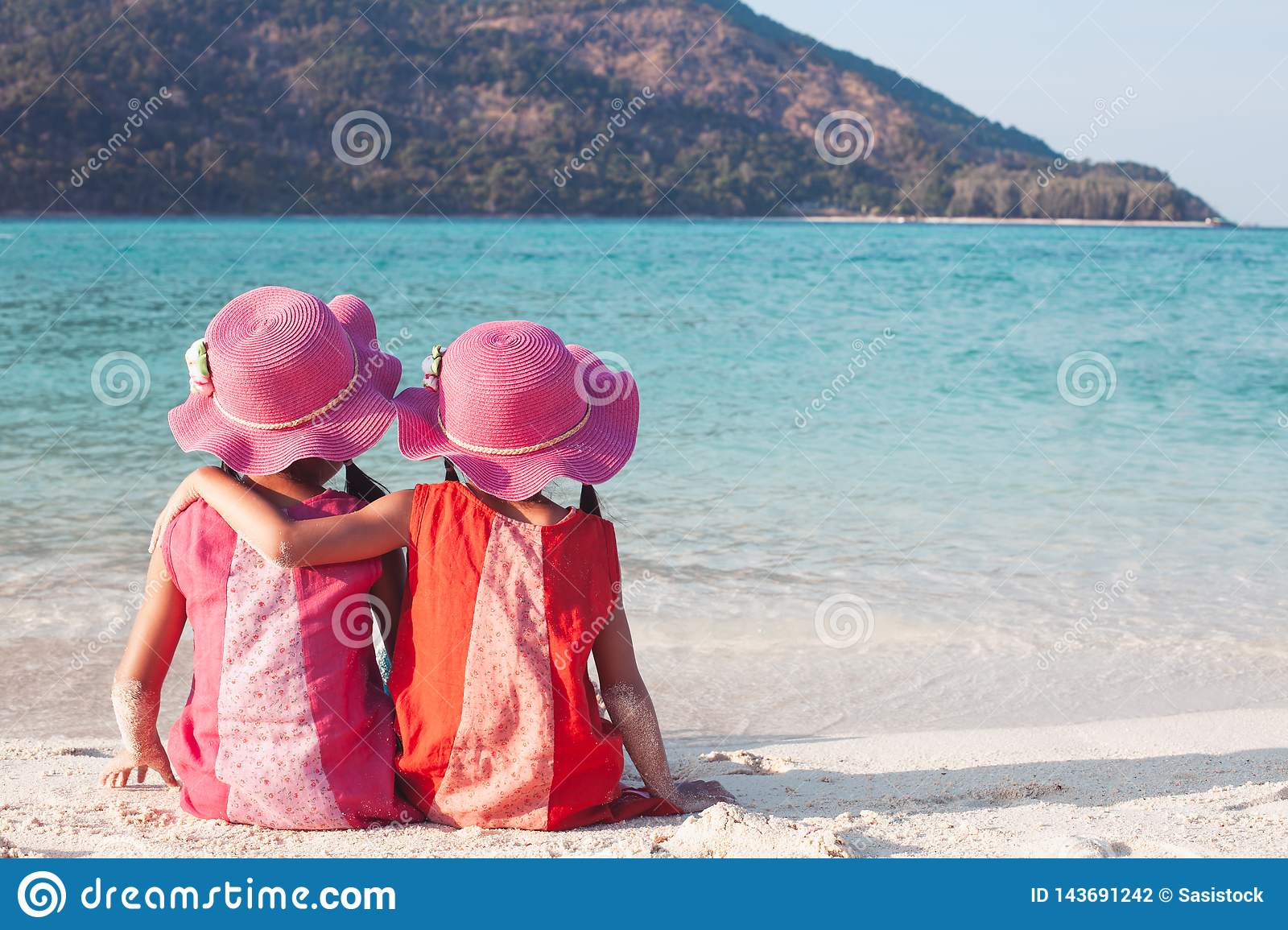 Two asian little child girls sitting and hugging each other  on the beach near the beautiful sea in summer vacation