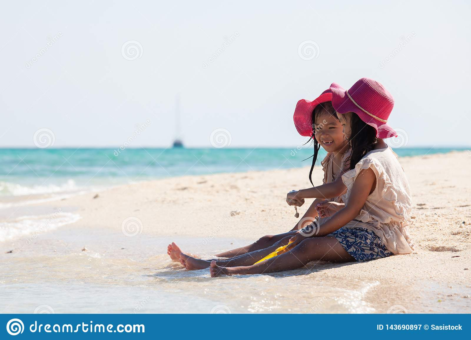 Two asian little child girls sitting and playing with sand together on the beach near the beautiful sea in summer vacation