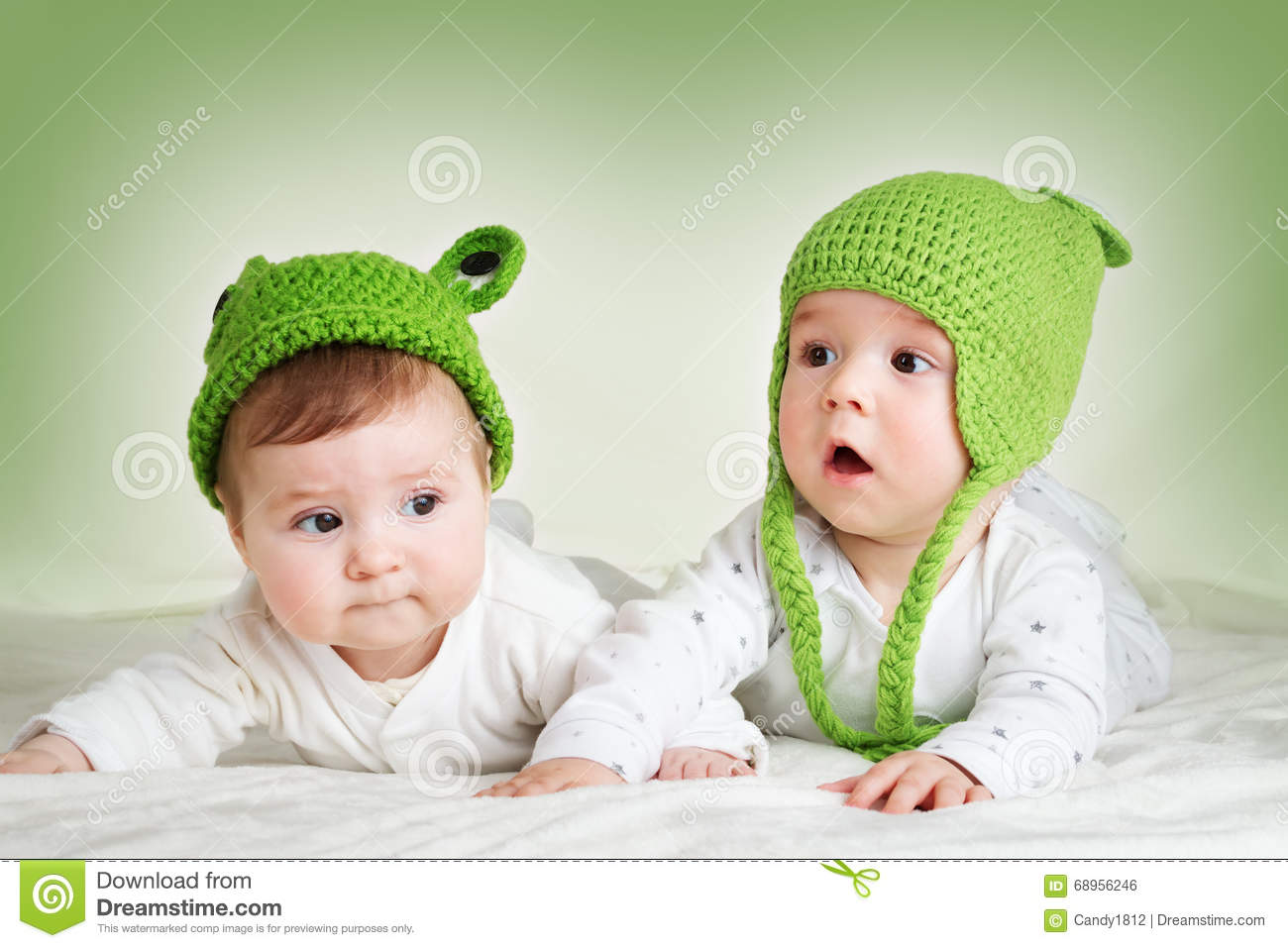 two cute babies lying in frog hats on spft blanket stock photo