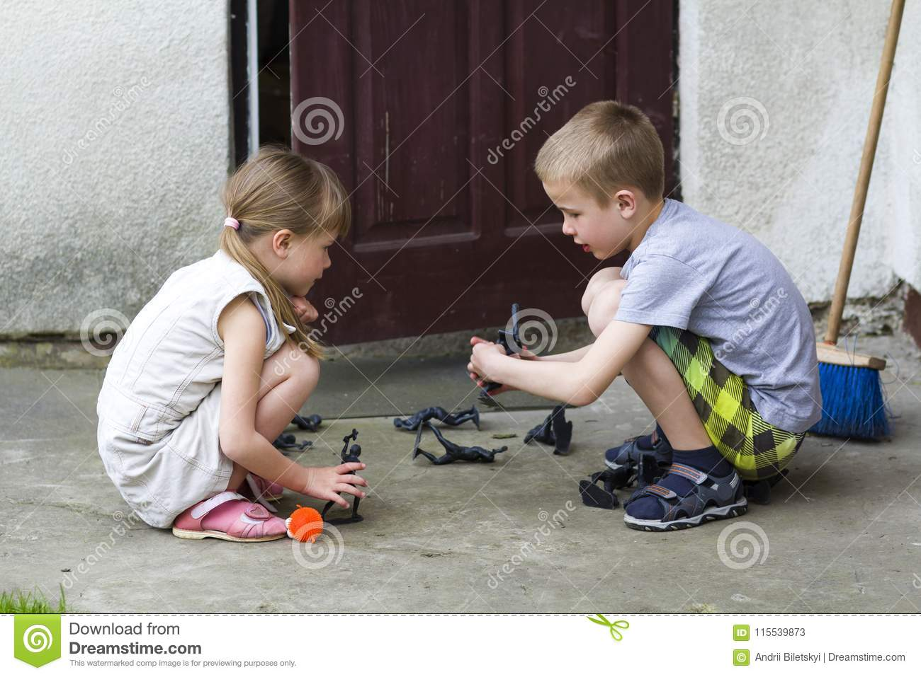 Two cute children blond pretty preschool girl and handsome boy playing outdoors with plastic toys on warm summer day on background