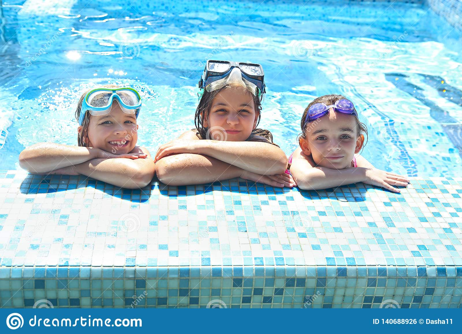 Two cute girls playing in swimming pool