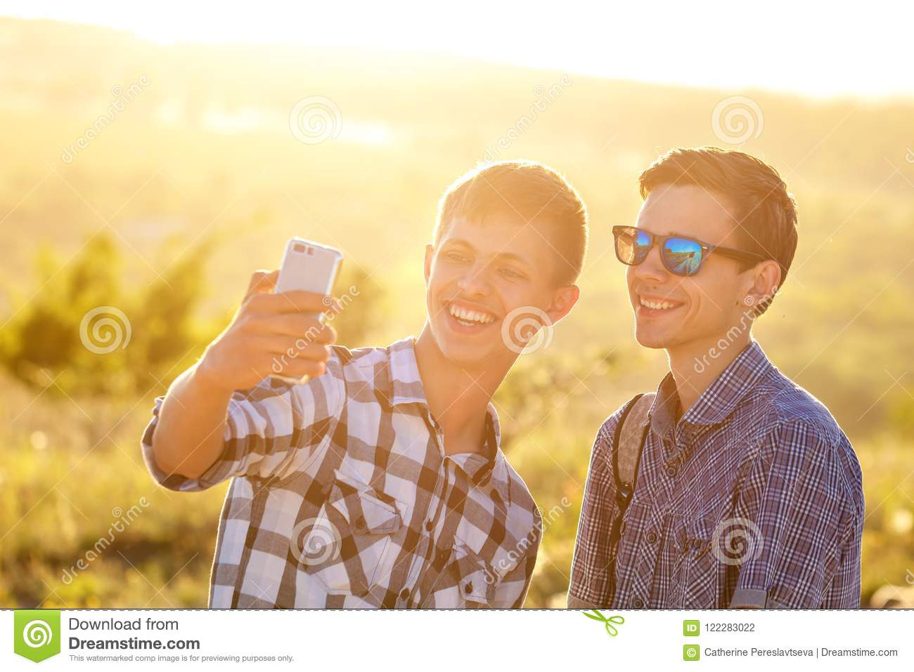 Two cute guys take selfies happy friends are photographed on the phone
