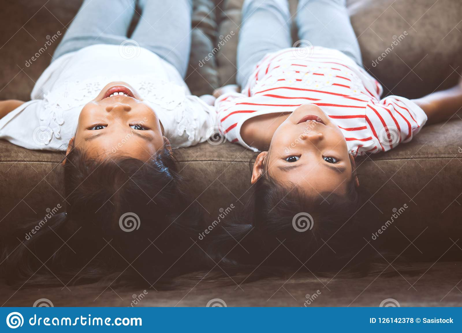 Two cute little child girls are lying on their backs on sofa