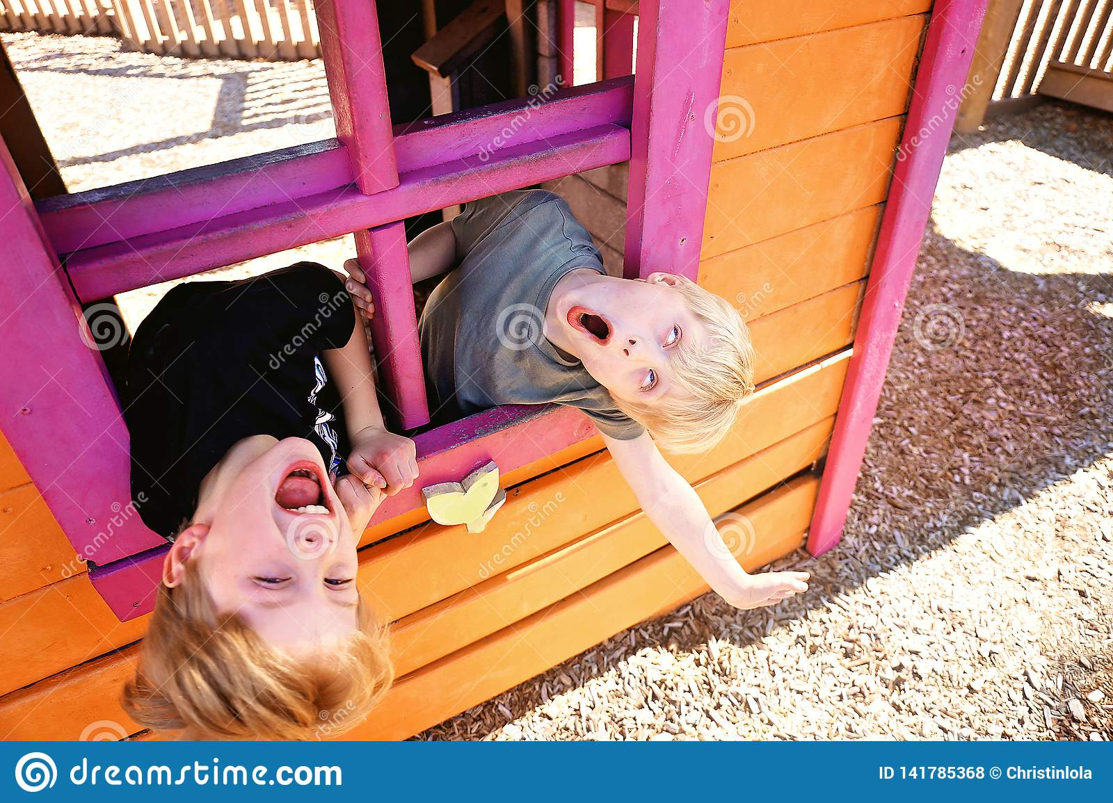 Two Cute Little Kids Playing Outside in a Club House at a Playground, Making Funny Faces