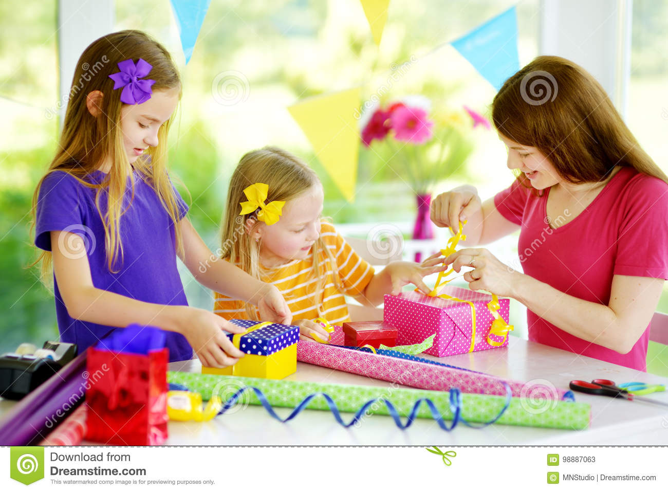Two Cute Sisters And Their Young Mother Wrapping Gifts In Colorful Paper Family Of Three Birthday Presents Fun