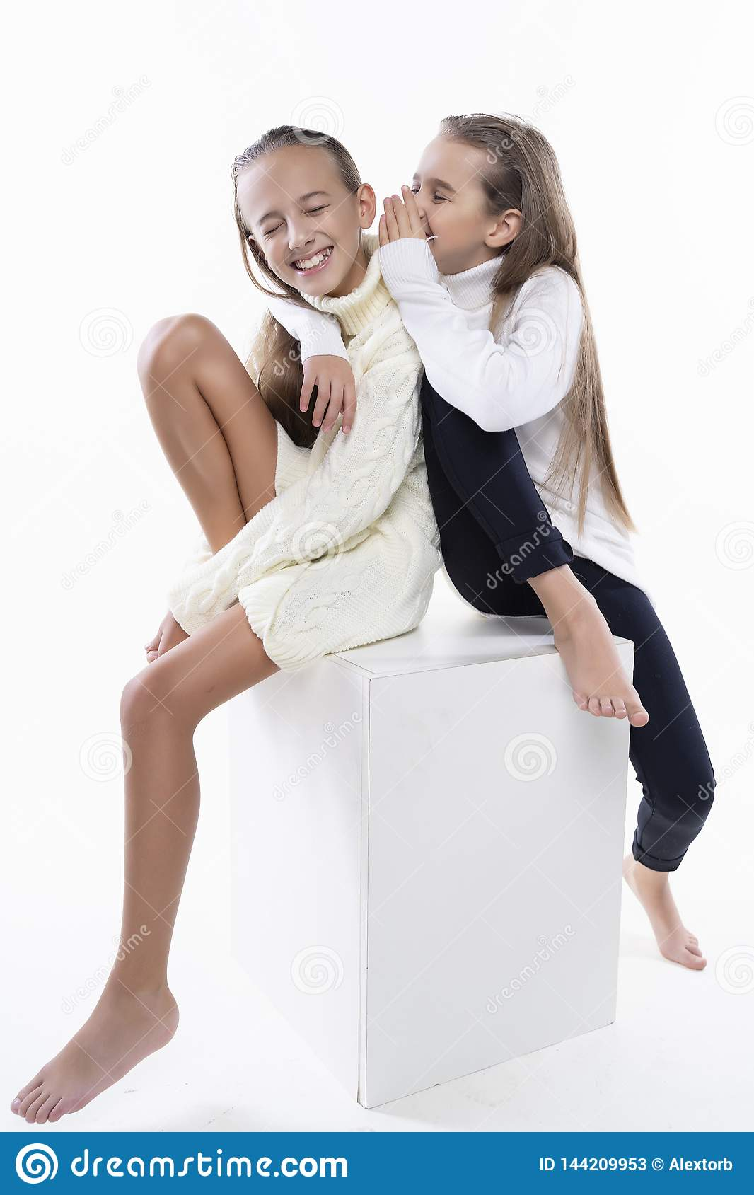 Two cute teenage girlfriends schoolgirls wearing white turtleneck sweaters, smiling sit back to back. on white. Fashion a