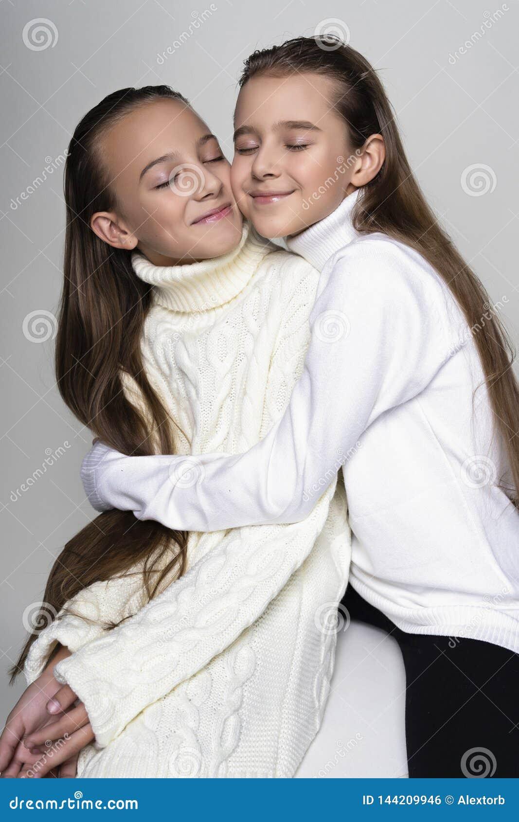 Two cute teenage girlfriends schoolgirls wearing white turtleneck sweaters, smiling sit, hugging each other in a friendly way.