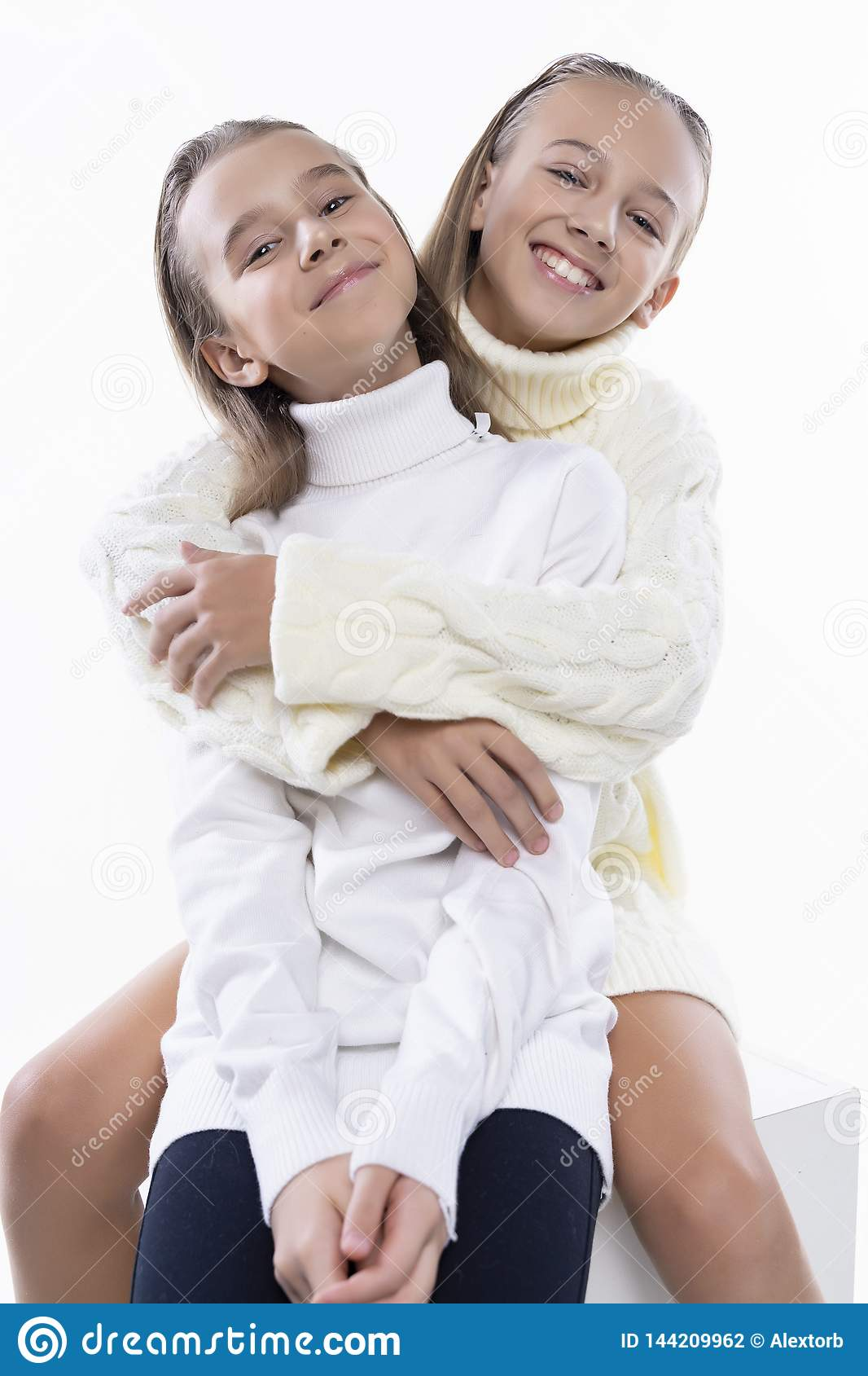 Two cute teenage girlfriends schoolgirls wearing white turtleneck sweaters, smiling sit, hugging each other in a friendly way.