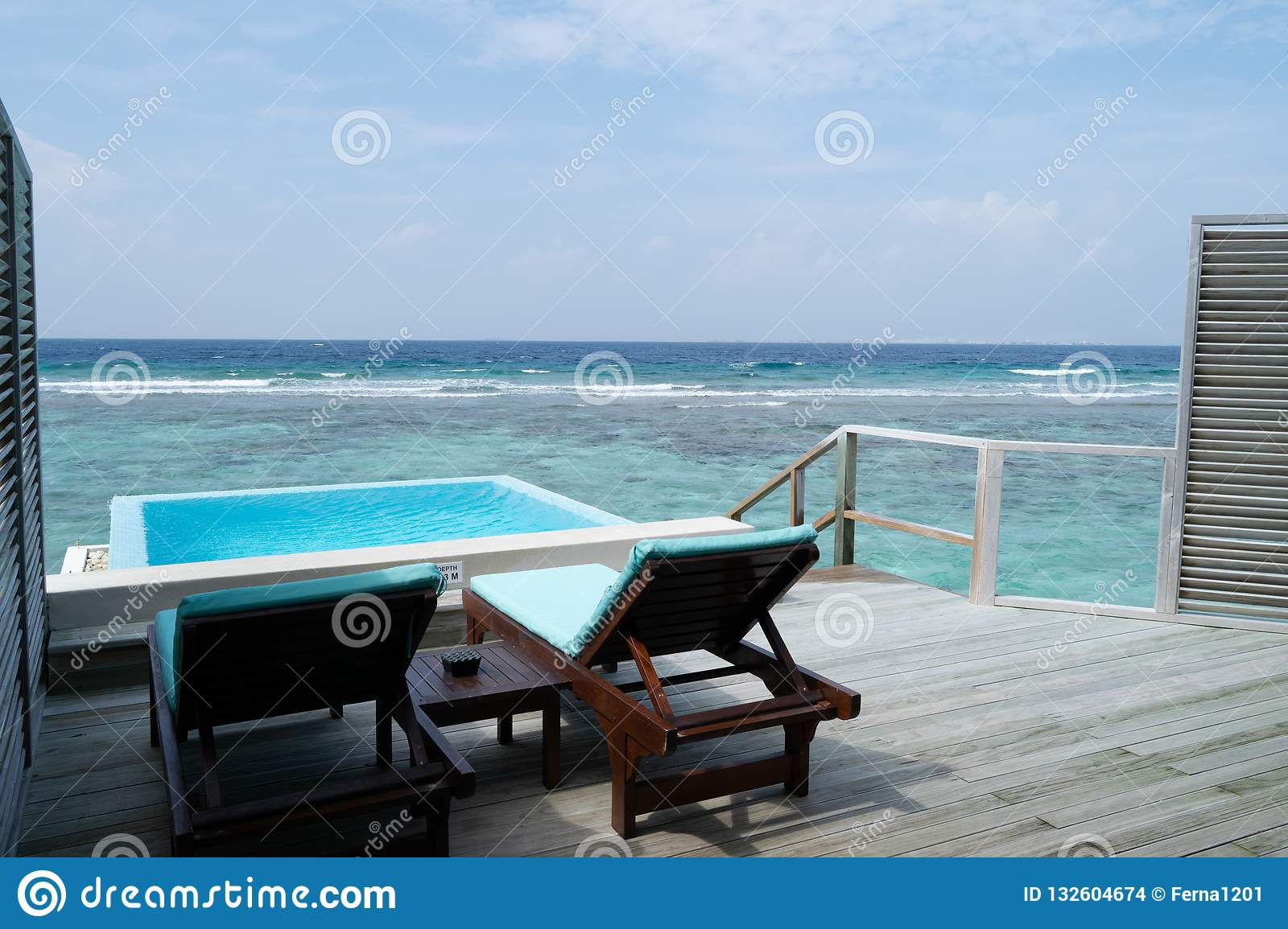 Two deckchair and a pool on the terrace on beautiful bungalow on
