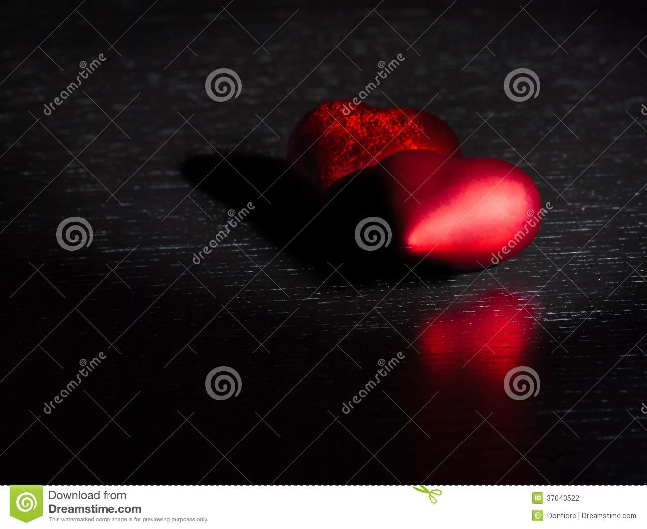 Two decorative red hearts on black dark light and on wood table, concept of valentine day