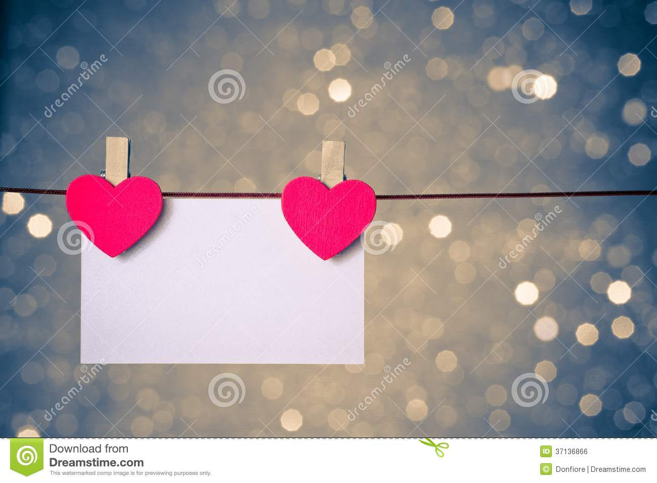 Two decorative red hearts with greeting card hanging on blue and golden light bokeh background, concept of valentine day