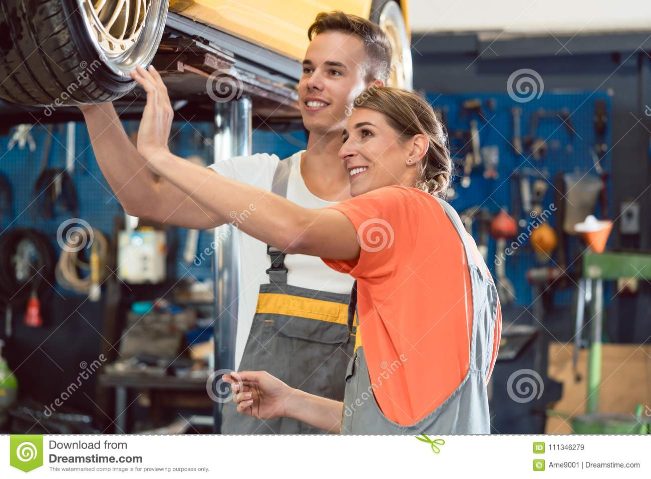 Two dedicated auto mechanics smiling while checking the wheels of a tuned car