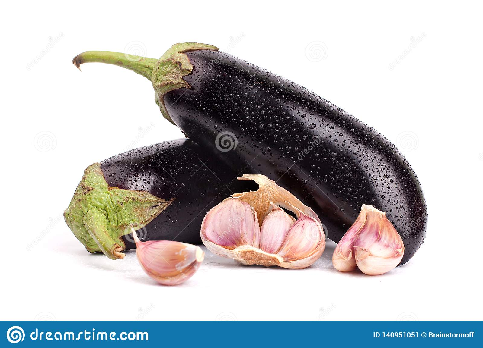 Two eggplants and garlic cloves in water drops with green tails on white background close up isolated