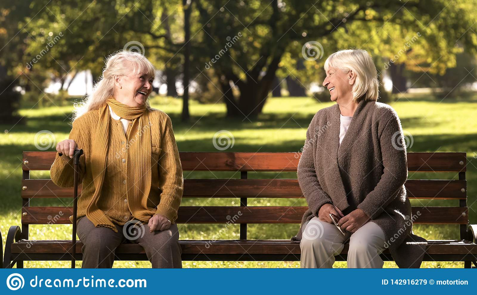Two elderly ladies laughing and talking, sitting on bench in park, old friends