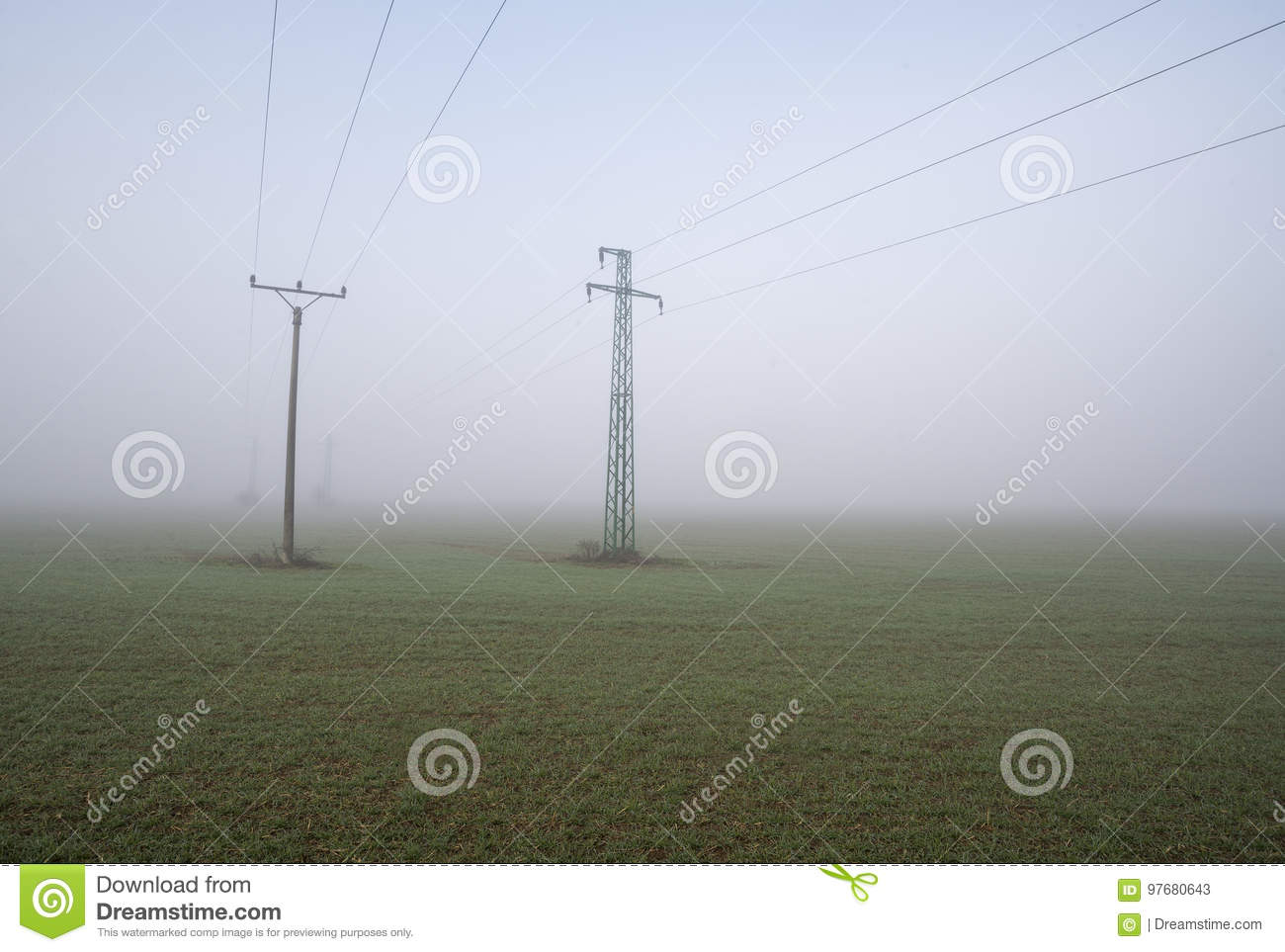 Two electric poles on the field in fog