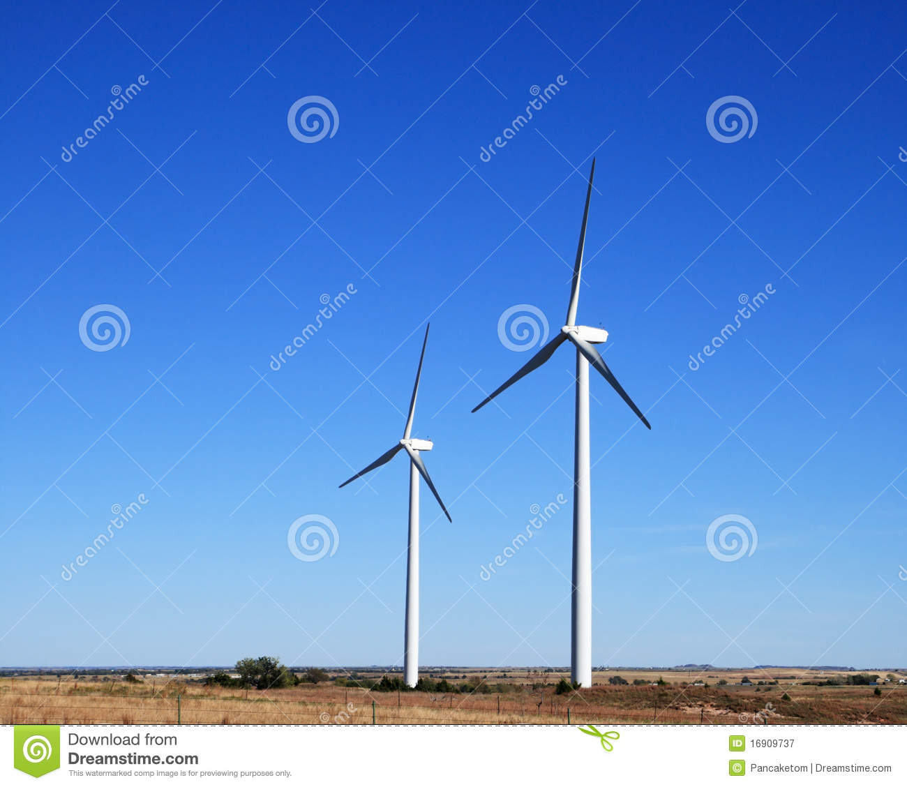 Two white electric windmills or wind turbines on a flat prairie with ...