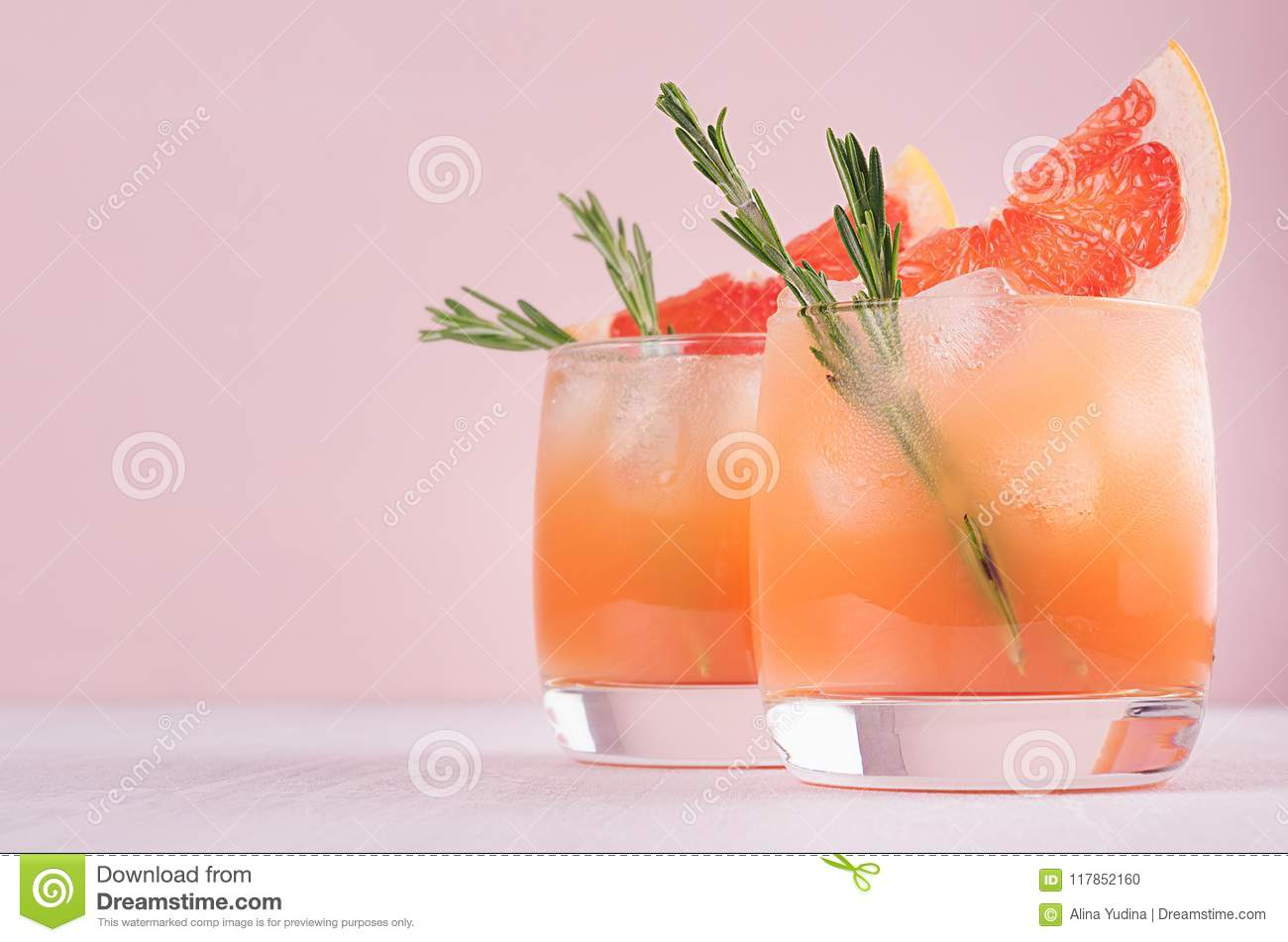 Two elegance cold wet drinking glasses with fresh grapefruit summer alcohol cocktail, ice, rosemary on fashion pink background.