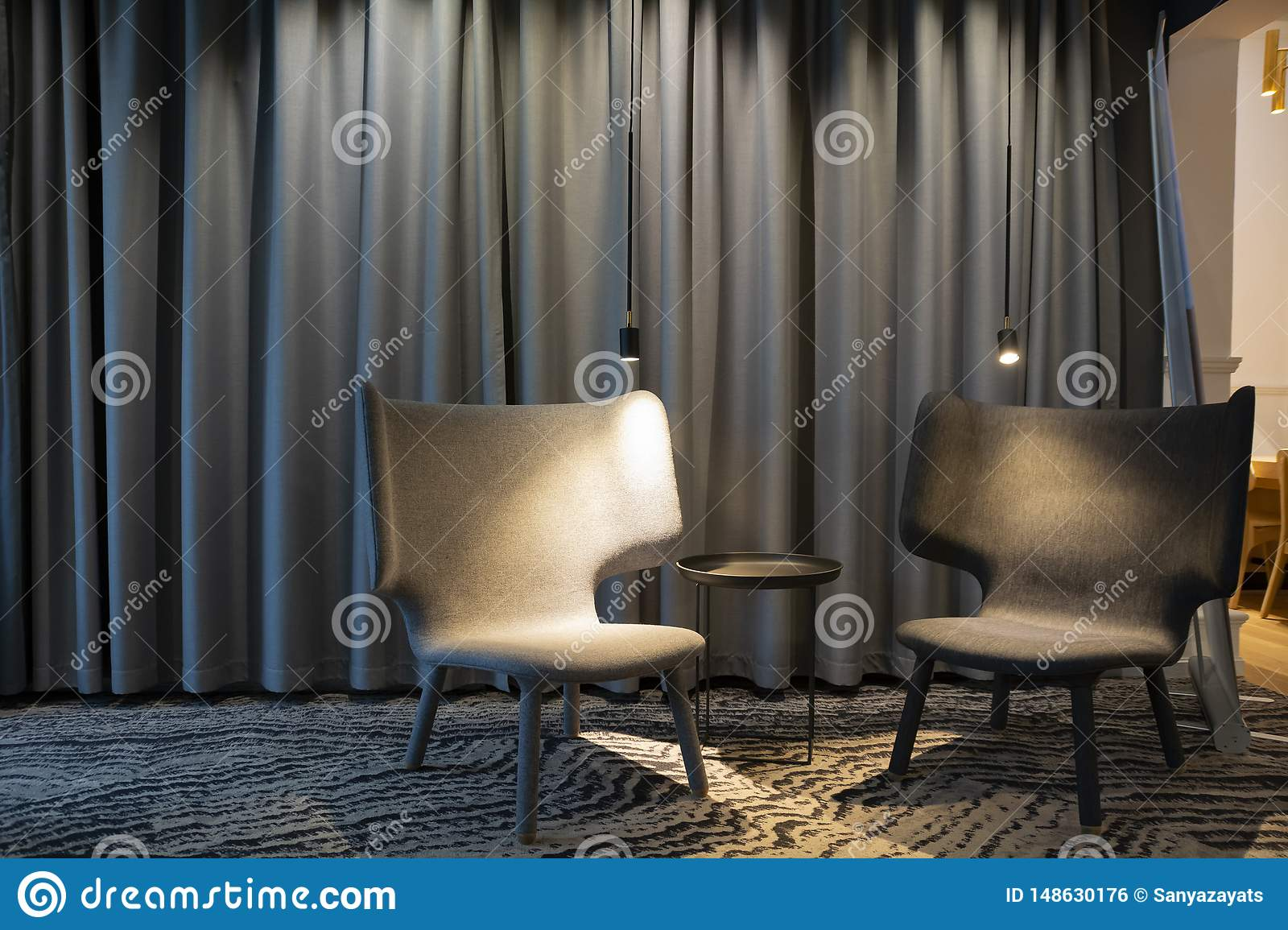 Two Empty Modern Grey Chair With Lights And A Table Between