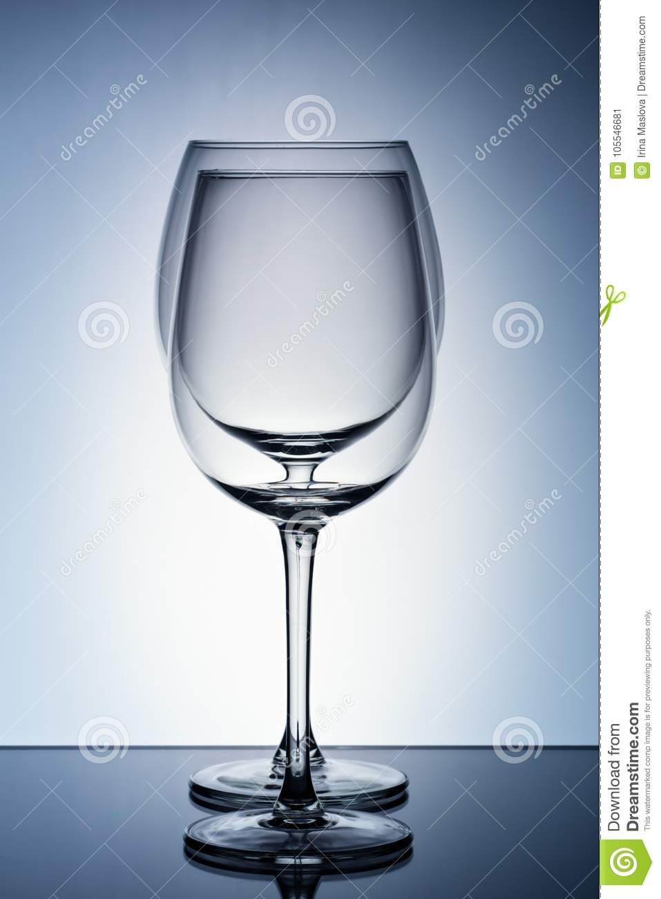 Two empty wineglass for red wine on diffusion lit background in abstract composition with reflection