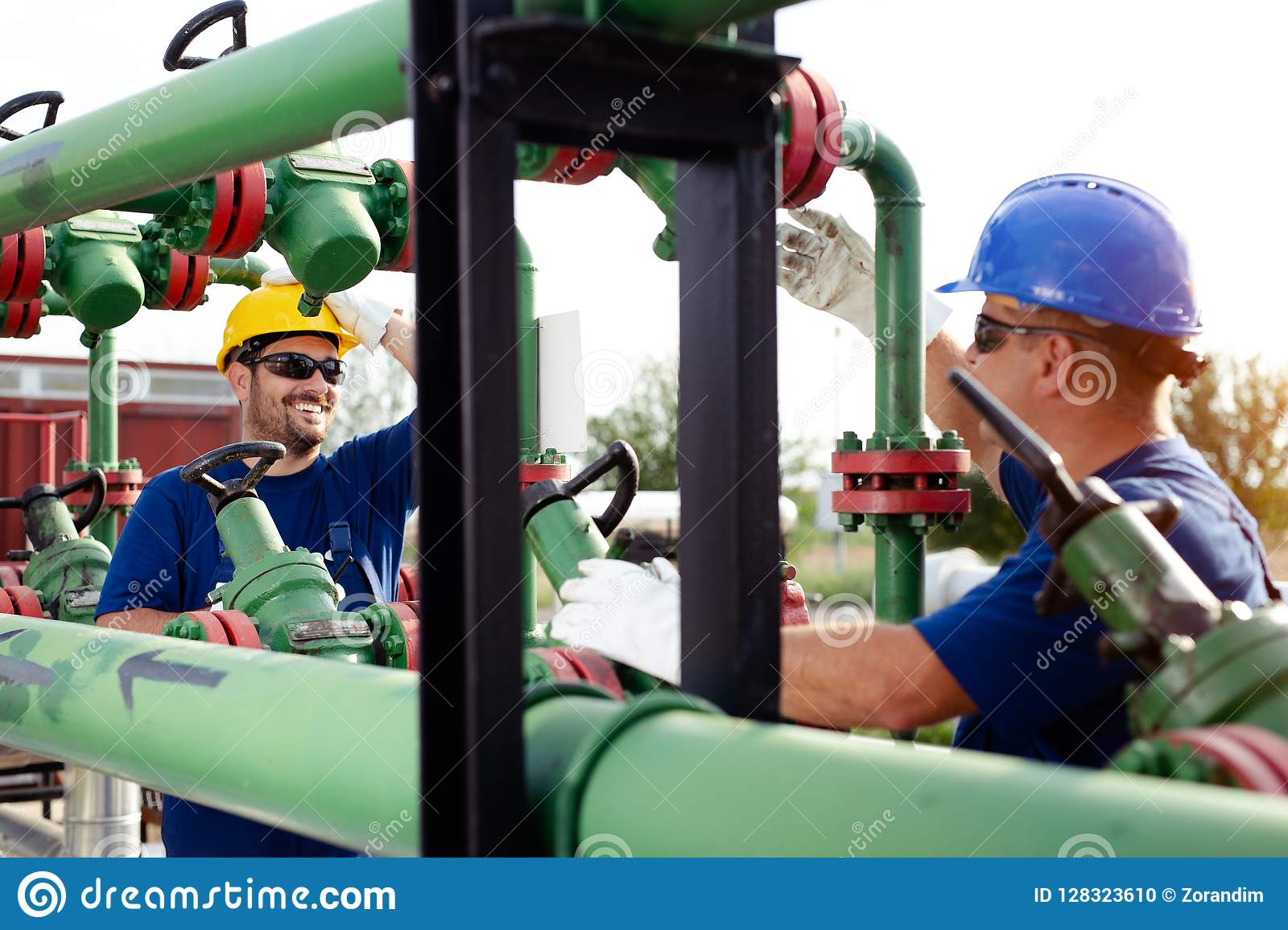 Two engineers working inside oil and gas refinery