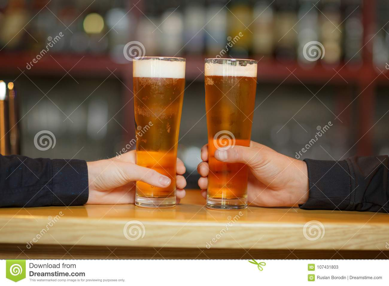 Two men cling to full glasses with a beer. Close-up.