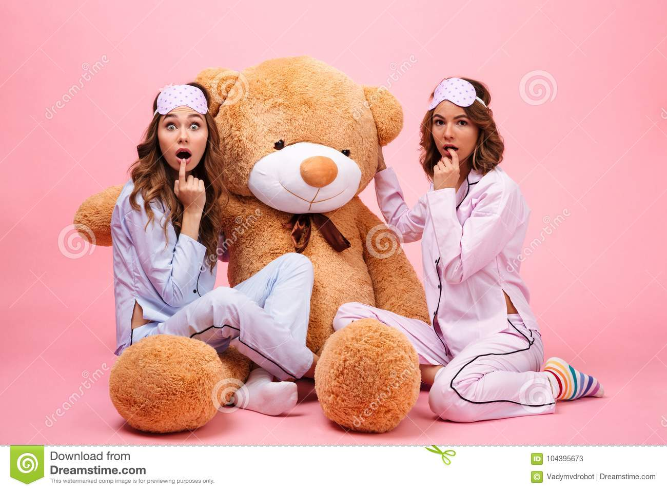 Two excited girls in pajamas sitting with a big teddy bear and looking at camera  isolated over pink 12d51f22c