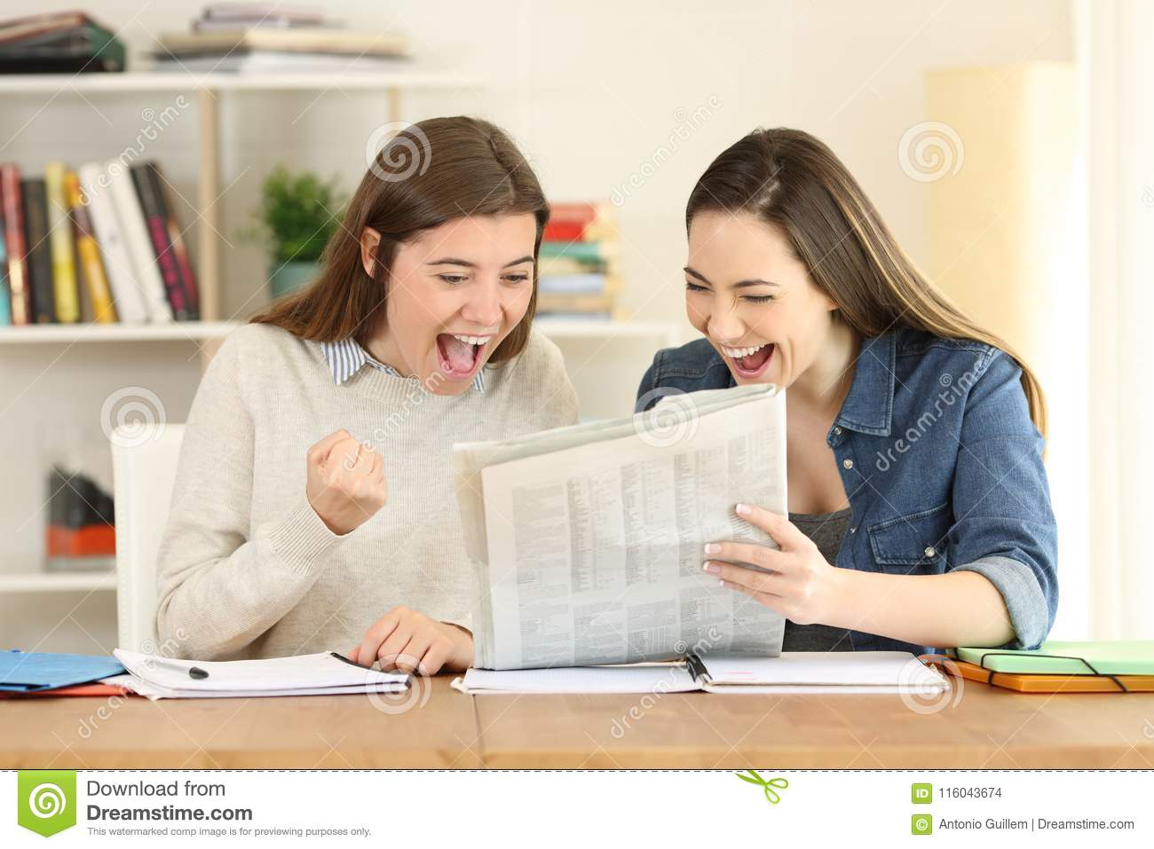 two excited students reading a newspaper stock photo - image of
