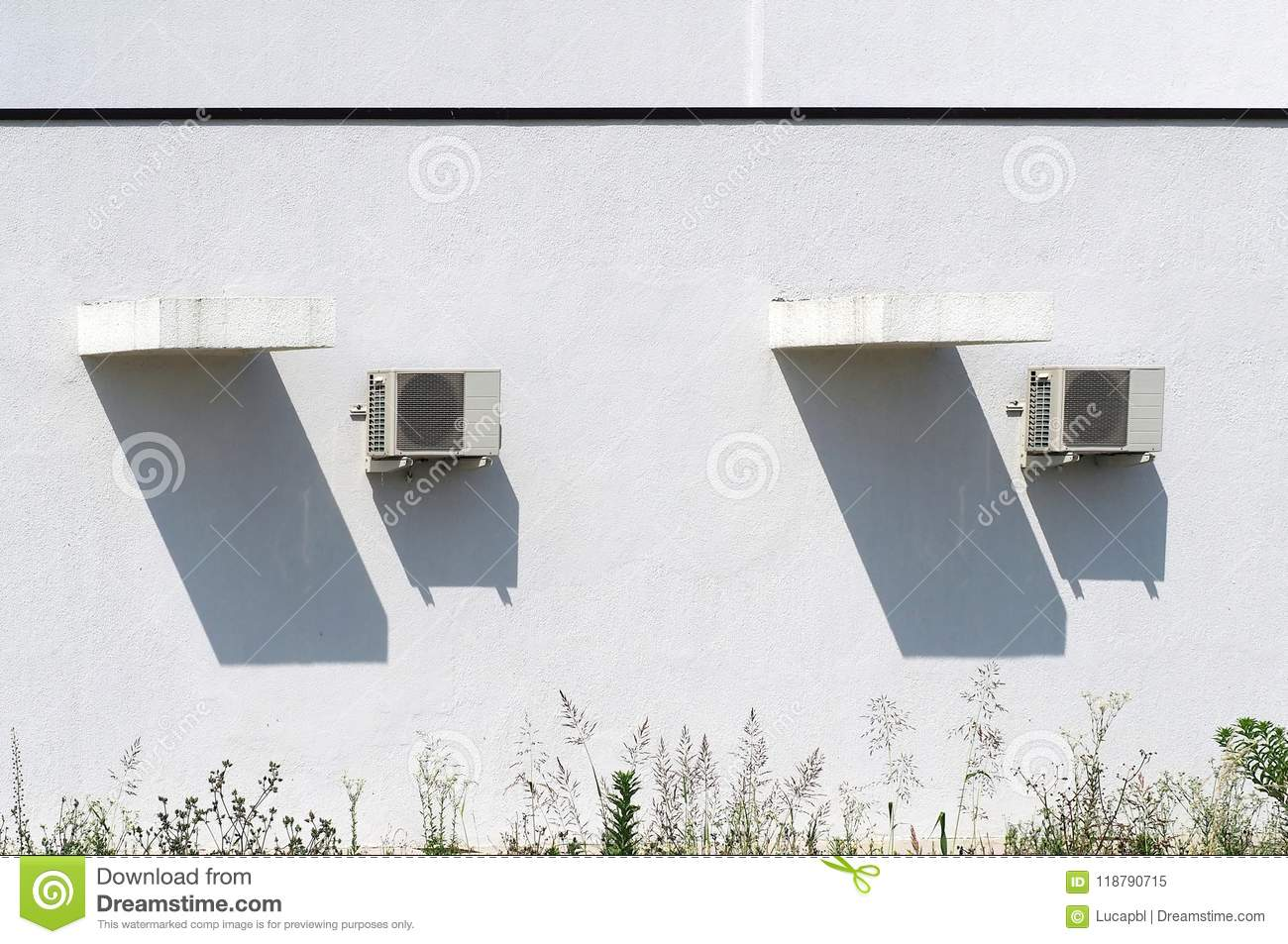 Two exteriors air conditioning units and their long shadows on a home white wall, under a hot summer sunny day