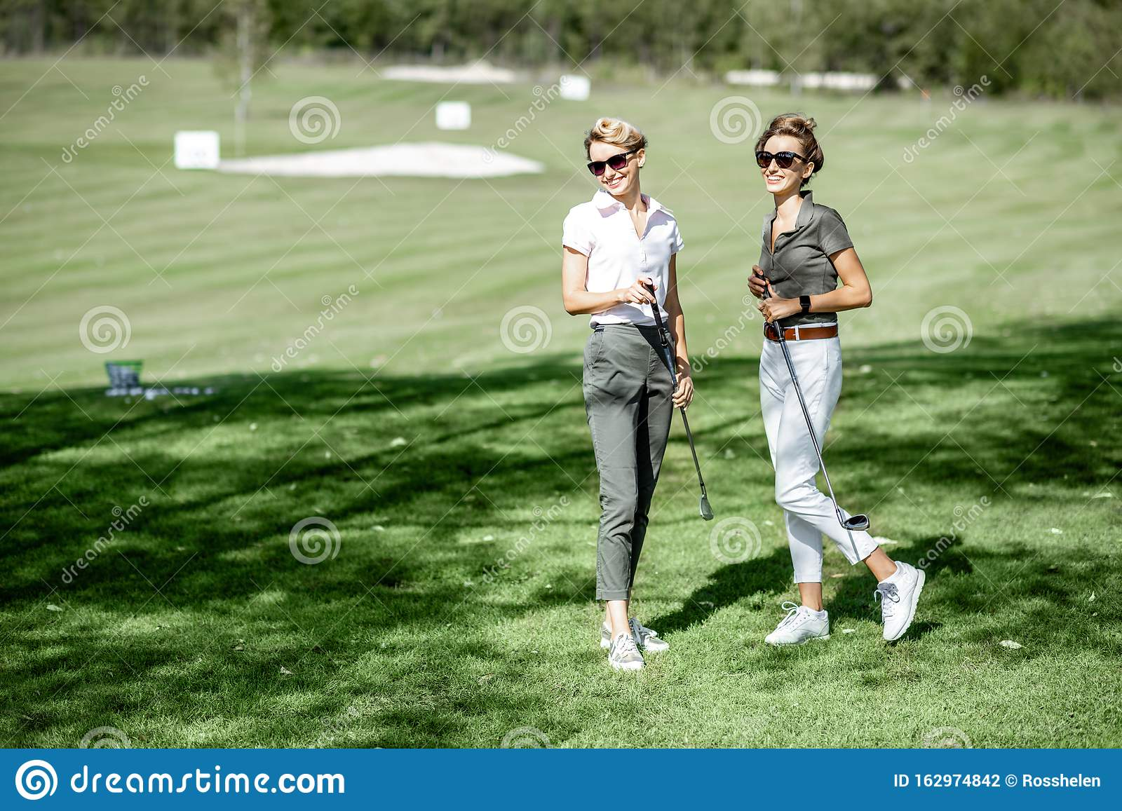 Two Female Golfers On Golf Course Stock Photo - Image of