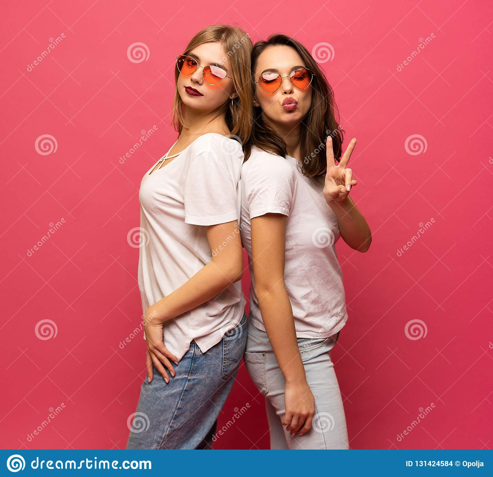 Two female friends hugging and having fun together, showing peace gesture while looking at camera, isolated over pink