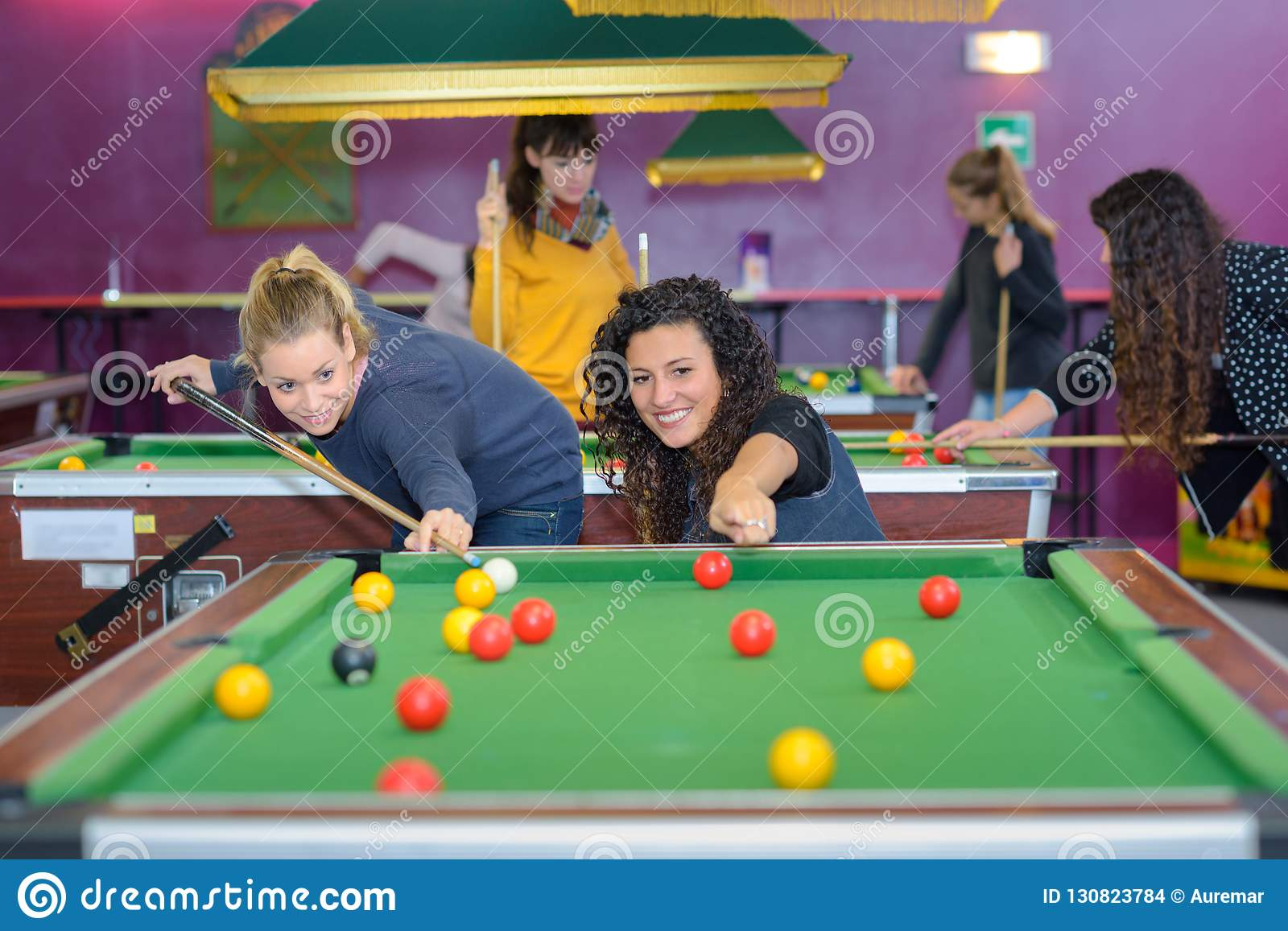 Two female friends playing billiards