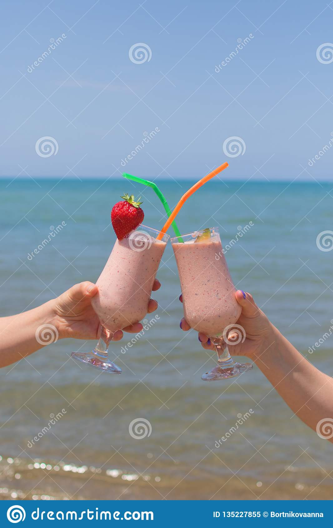 Two female hands are holding strawberry milkshakes on the background of the sea