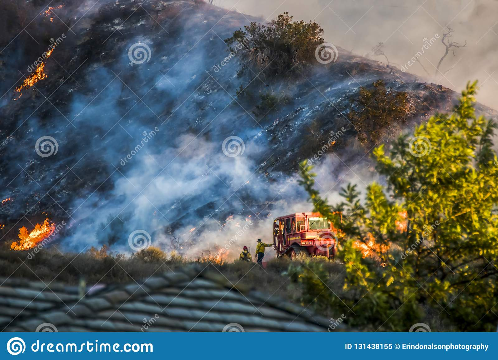 Two Firefighters Stand Next to Bulldozer with Hillside Burning in Background during California Fire