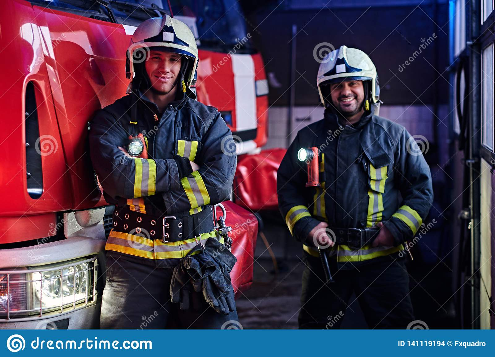 Two firemen wearing uniform standing next to a fire engine in a garage of a fire department, smiling and looking at a