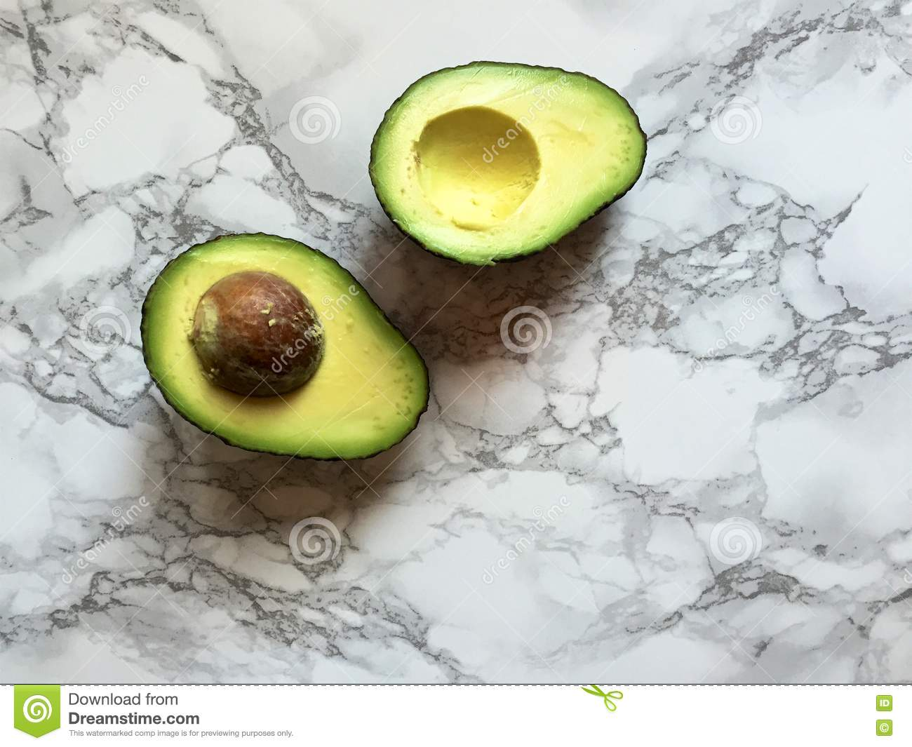 Two fresh avocado halves with pit on marble kitchen countertop