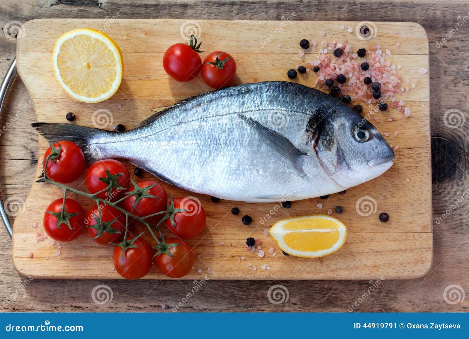 Two fresh gilt head bream fish on cutting board stock for Fish cutting board