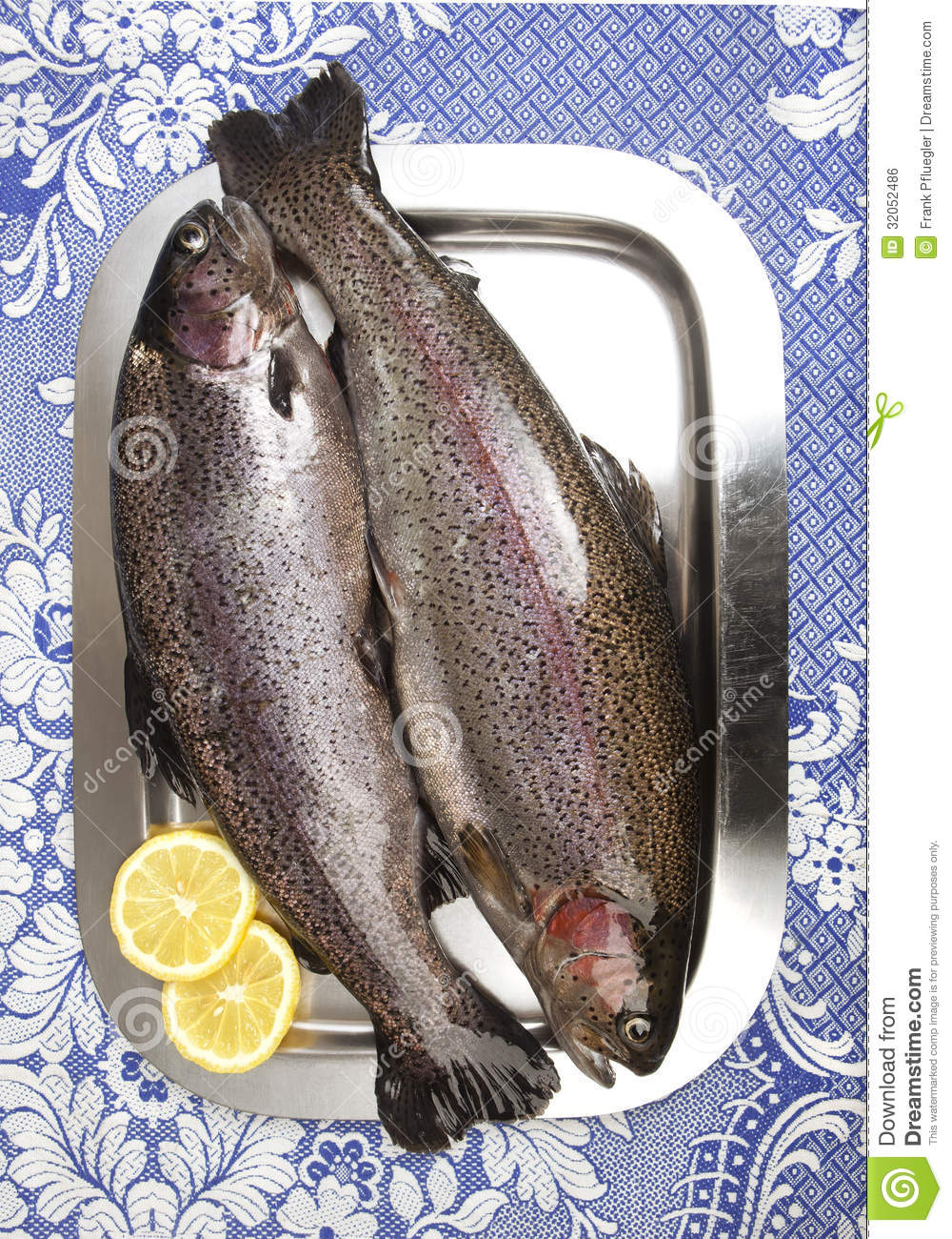 Two fresh rainbow trouts on a stainless steel tray