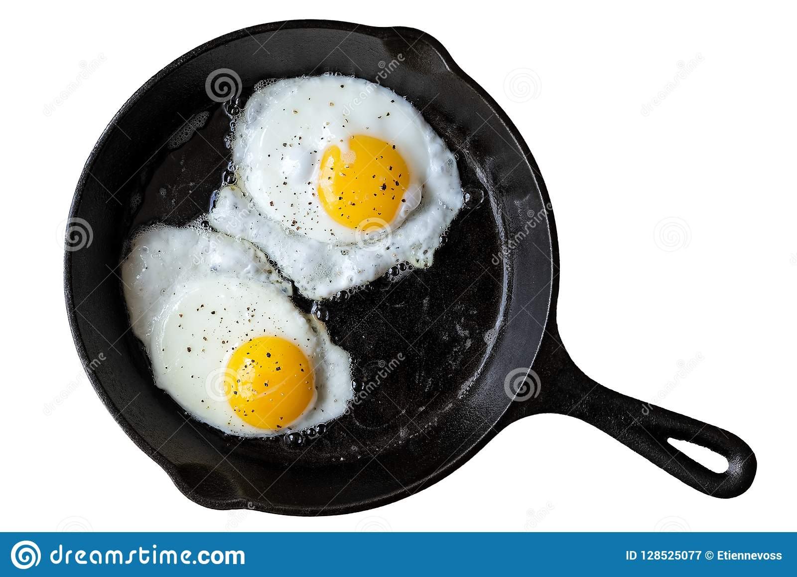 Two fried eggs in cast iron frying pan sprinkled with ground black pepper. Isolated on white from above.