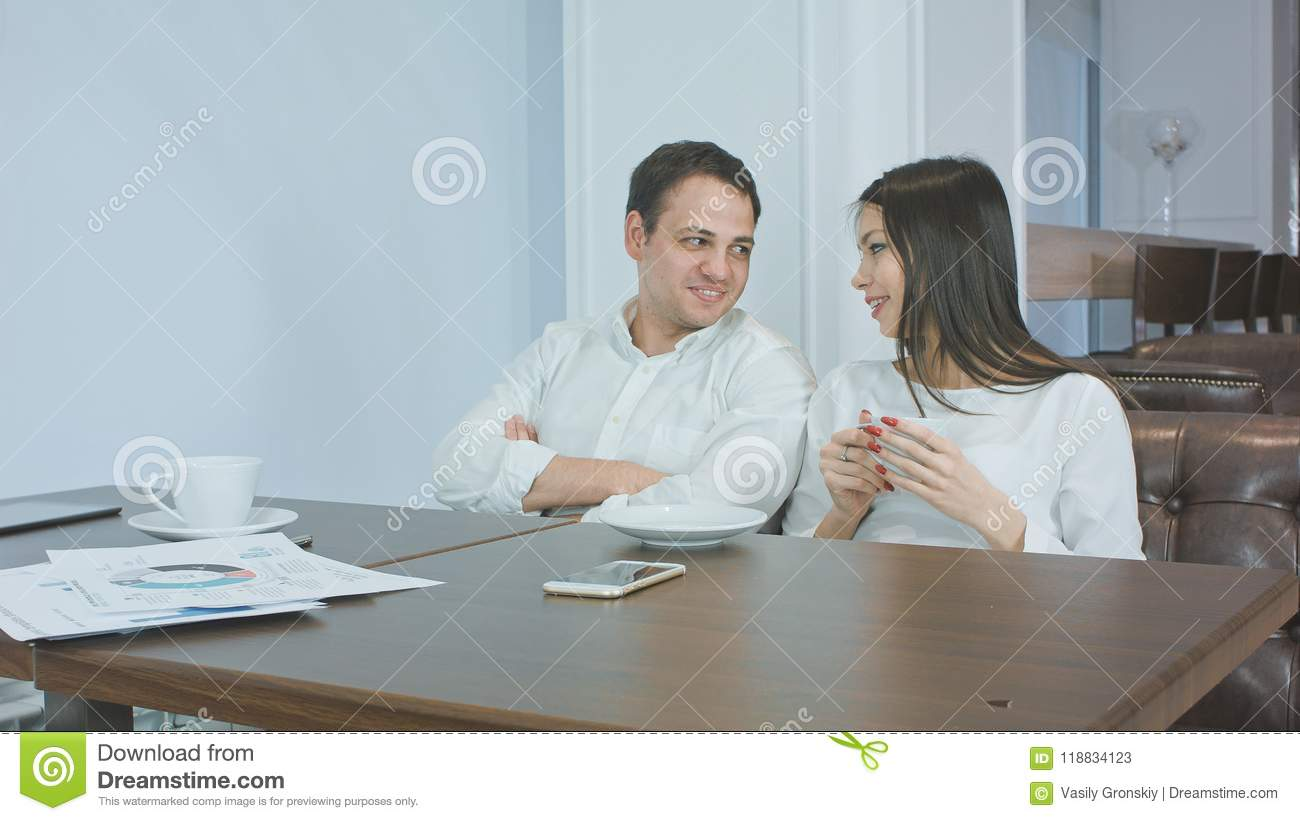 Two friendly colleagues talking and drinking coffee in a cafe