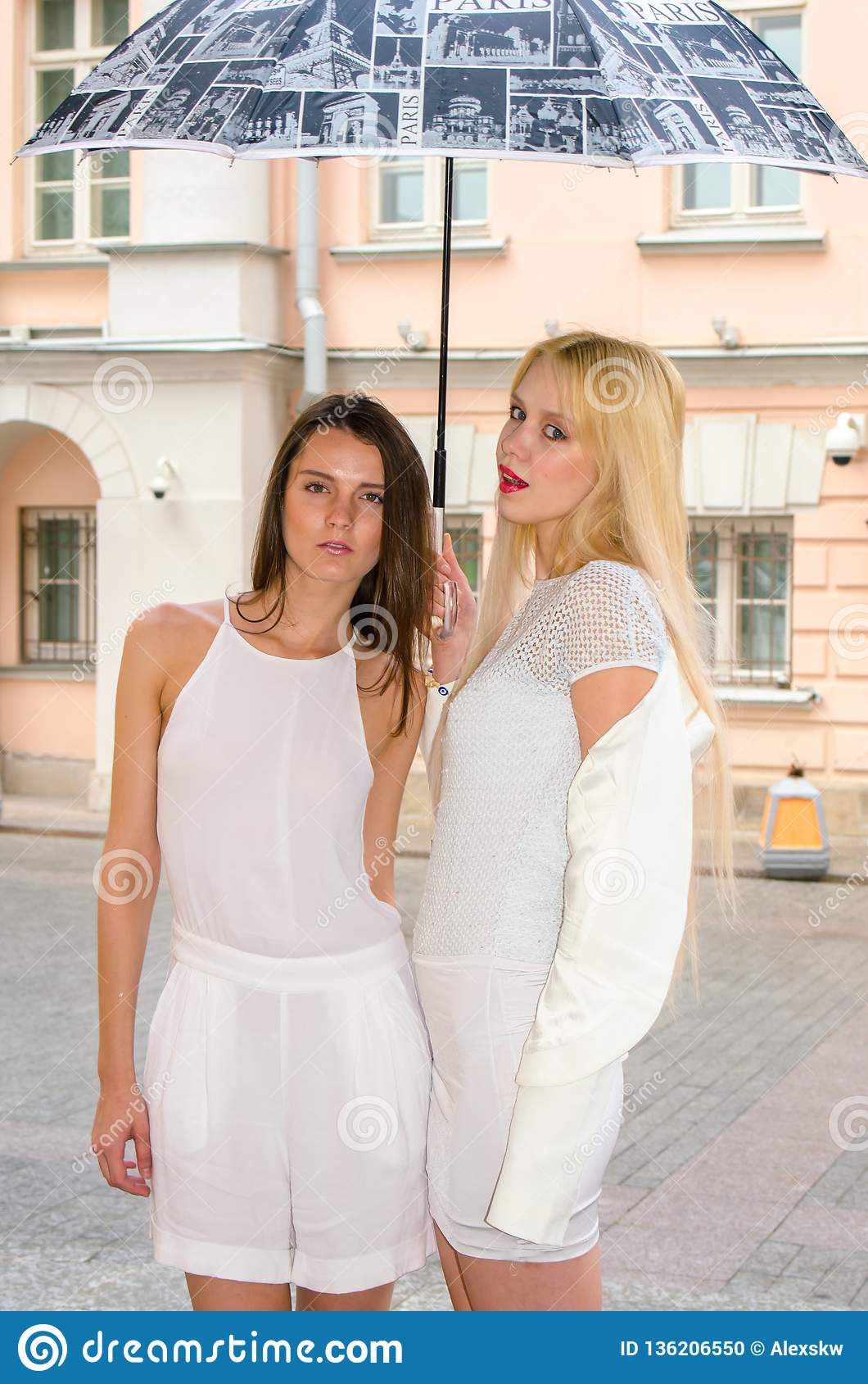 Two friends blonde and brunette in white dresses hiding from the weather under a large umbrella in the alleys of the old city