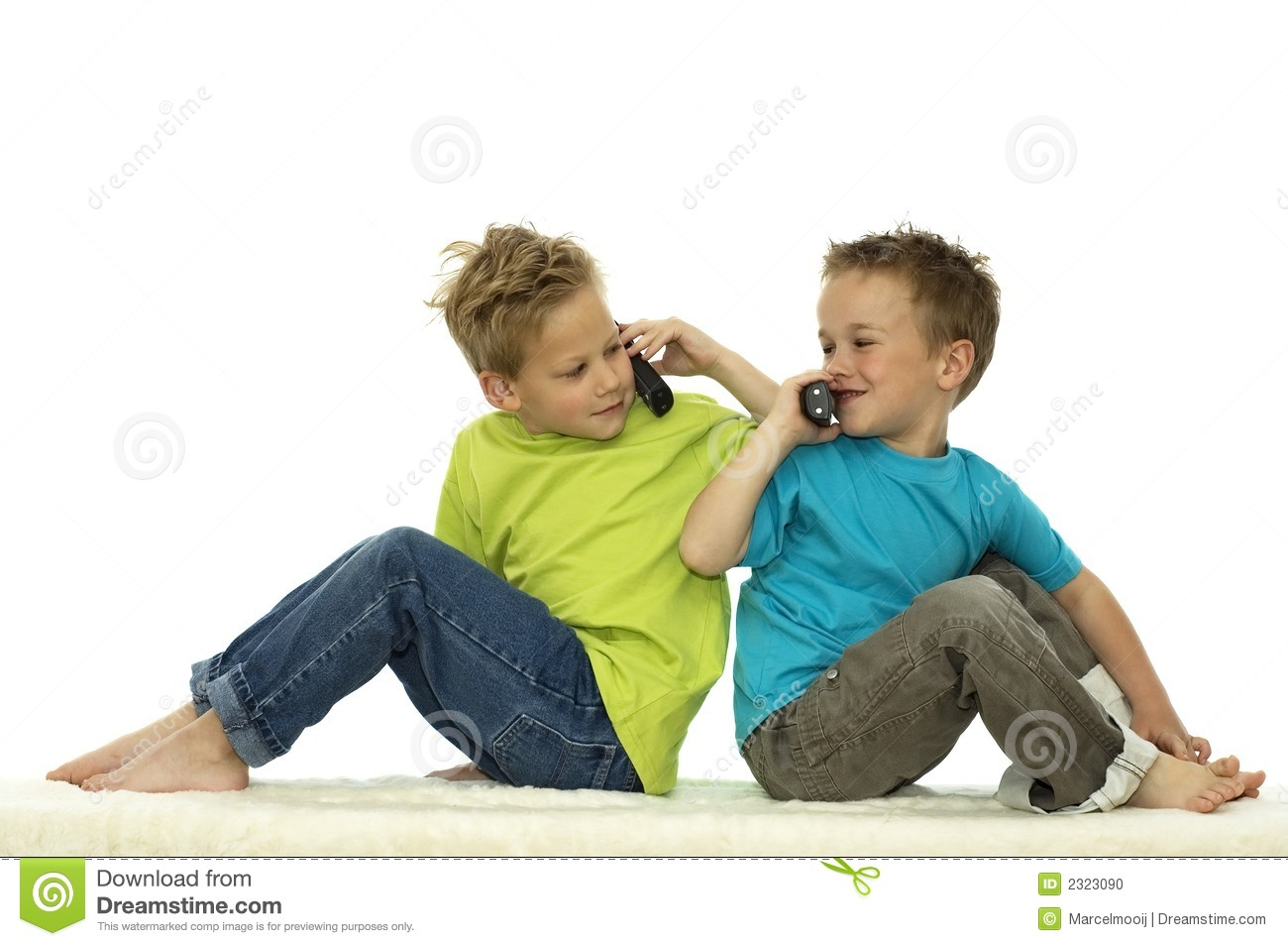 Two friends calling each other on their mobile phones while sitting ...