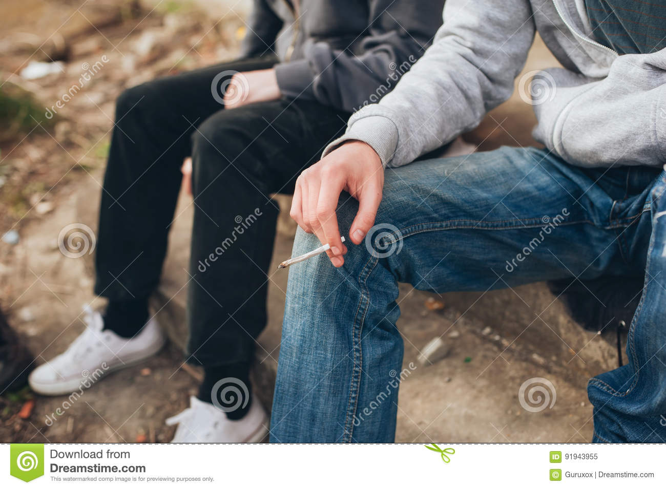 Two friends smoking joint in abandoned ghetto part of city