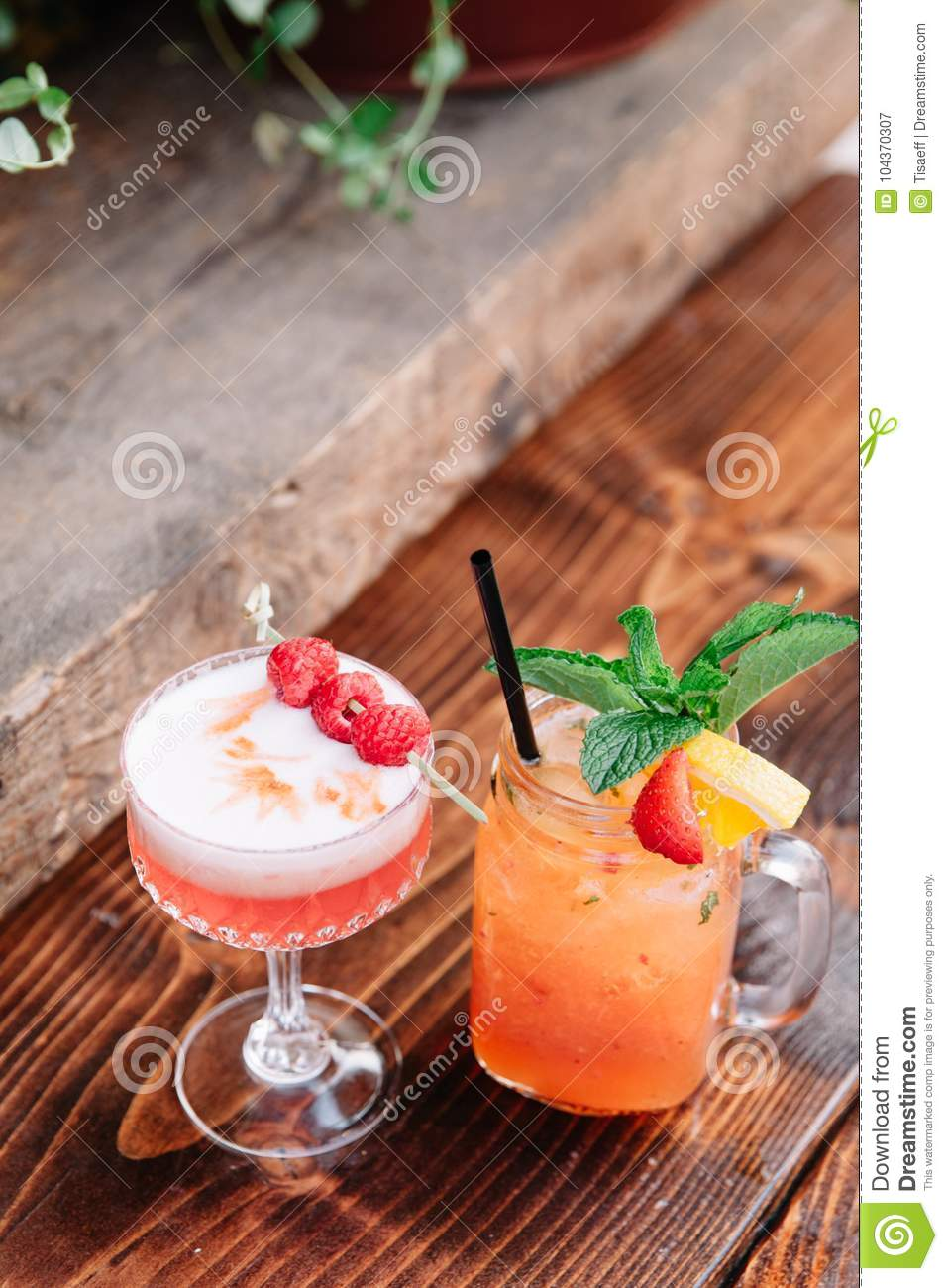 Two alcoholic cocktails garnished with berries and mint