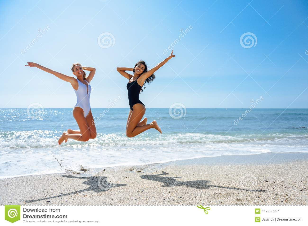 b059a0a96160d Two Funny Girls In Swimsuit Jumping On A Tropical Beach Stock Image ...