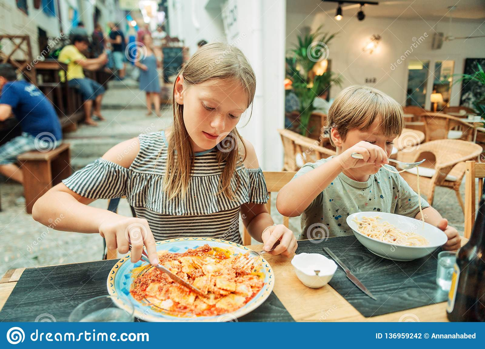 Two funny kids having lunch in the restaurant