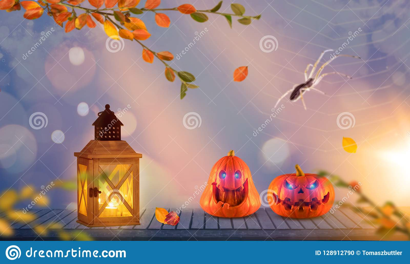 two funny scary orange halloween pumpkins with glowing eyes onh wood