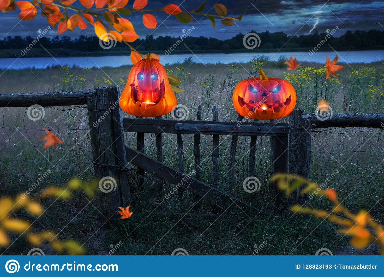 Two funny scary orange pumpkins with glowing eyes on wooden fence at halloween thunderstorm night