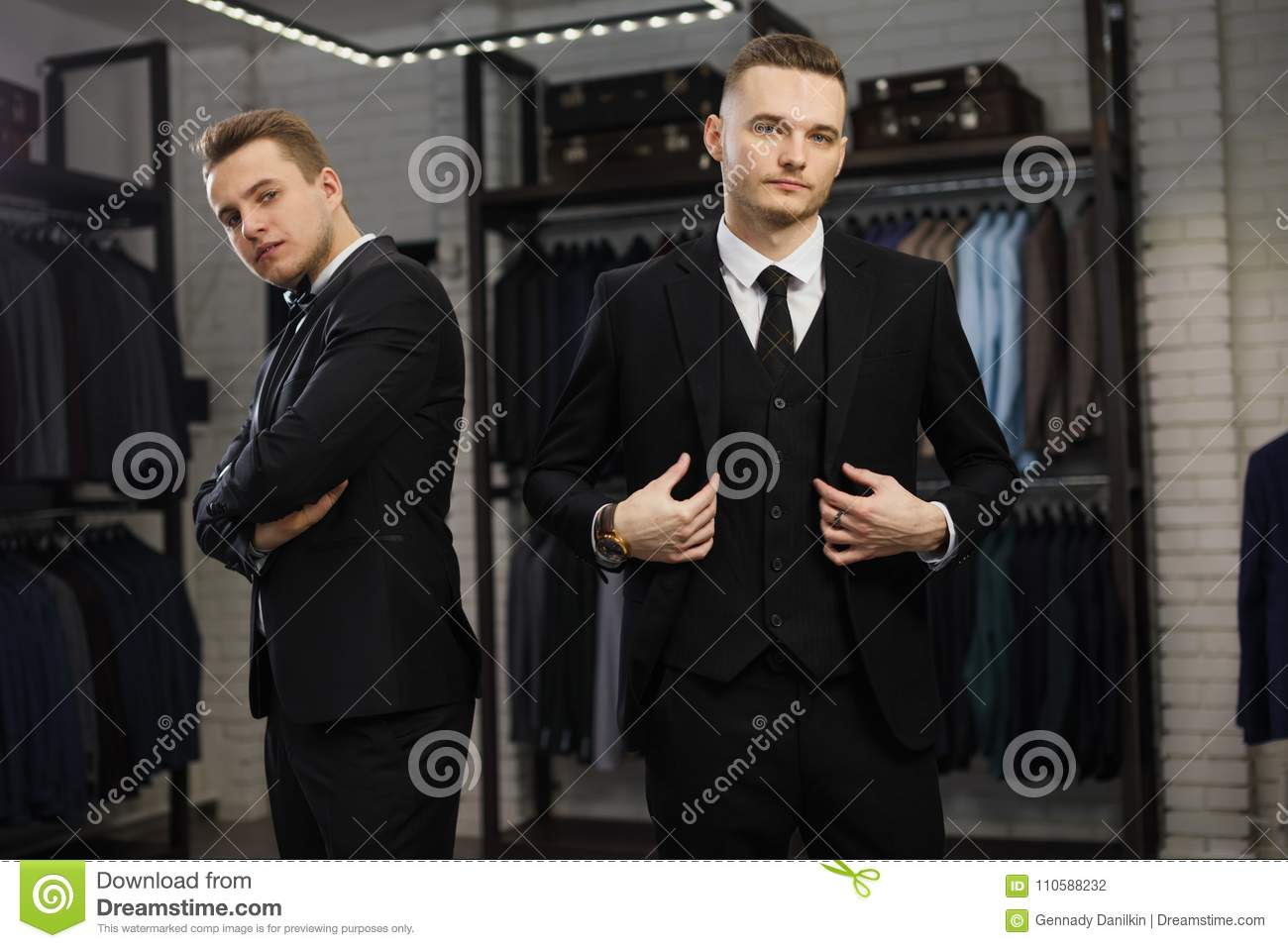 Two gay friends in classic vest against row of suits in shop