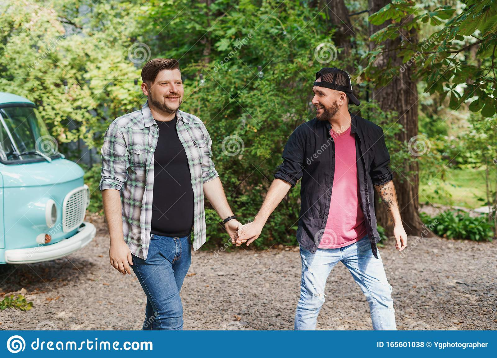 Two Gay Men Walk Holding Each Other`s Hands Stock Photo