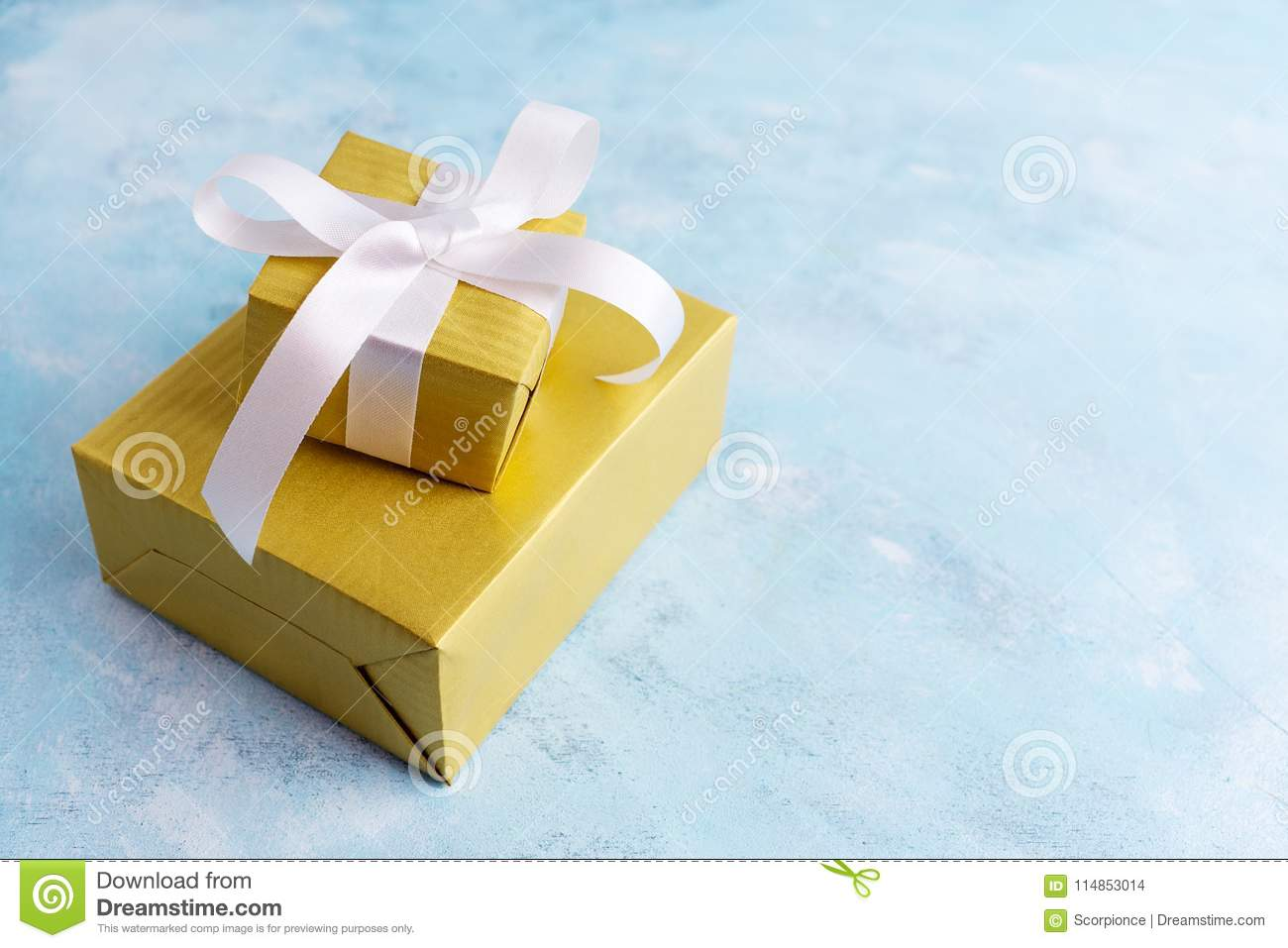 Two Gift Boxes In Gold Paper Witn White Bow On Blue Background